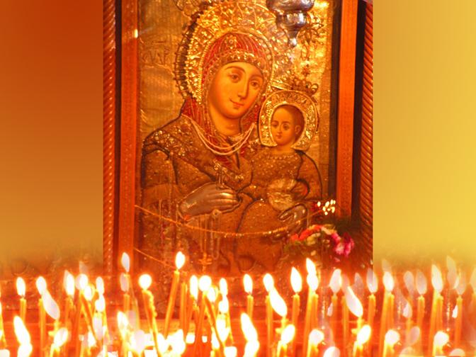Bên trái bàn thờ có hình Đức Mẹ và Chúa Hài Đồng với nến cháy lung linh